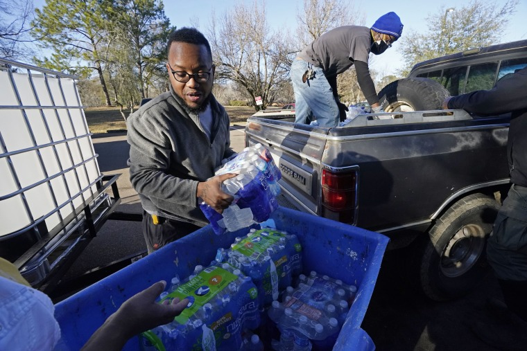 Image: Madonna Manor maintenance supervisor Lamar Jackson left, stacks bottled water brought by Mac Epps of Mississippi Move, as part of the supply efforts by city councilman and State Rep. De'Keither Stamps to a senior residence in west Jackson, Miss., o