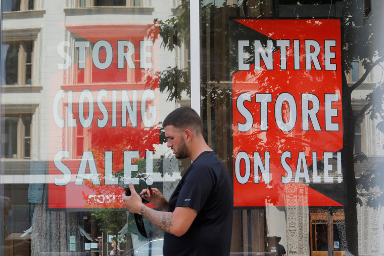 A man walks past signs in the windows of Lord & Taylor, advertising a store closing sale, in Boston