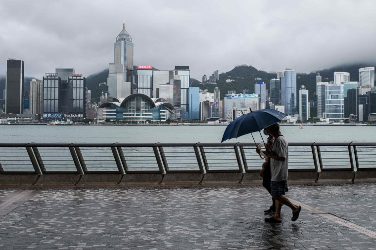 Image: Two pedestrians using umbrellas on a promenade that runs along Victoria Harbour in Hong Kong.