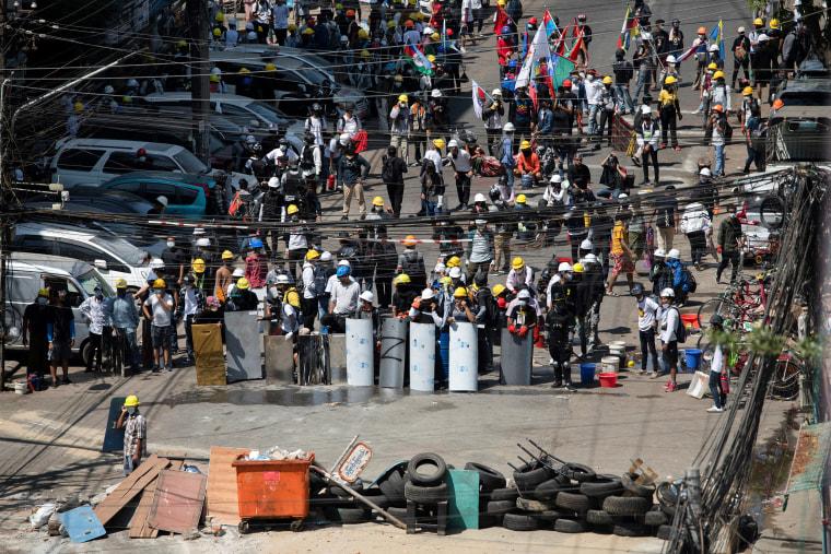 Image: Demonstrators block a road during an anti-coup protest in Yangon, Myanmar,