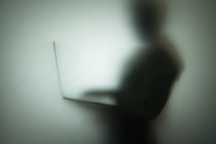 Silhouette of person using laptop, behind glass