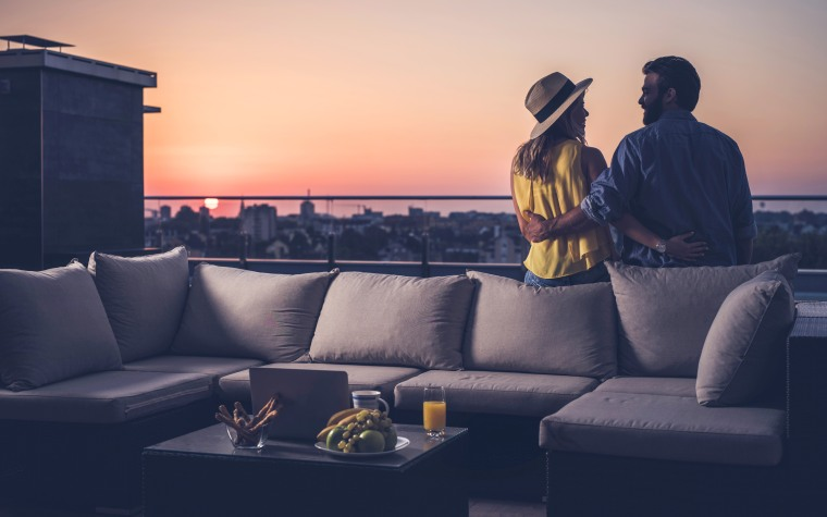 Rear view of happy couple communicating on a penthouse balcony at sunrise.