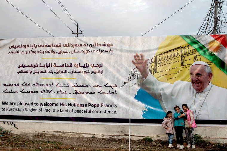 Image: Girls take a selfie in front of a poster promoting the upcoming trip of Pope Francis on March 4, 2021 in Irbil, Iraq.