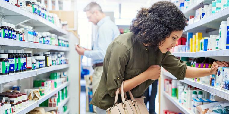 Image: Woman shopping at pharmacy, store shelfs