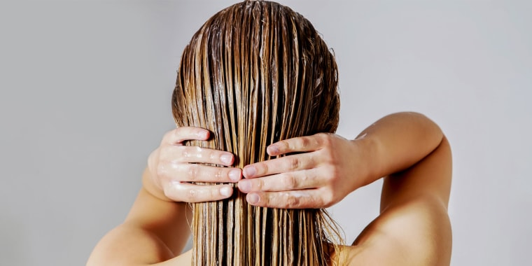 Woman rubbing hair mask in her blond hair