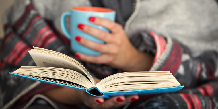 Woman holding a coffee mug and reading a popular memoirs, selected by Goodreads