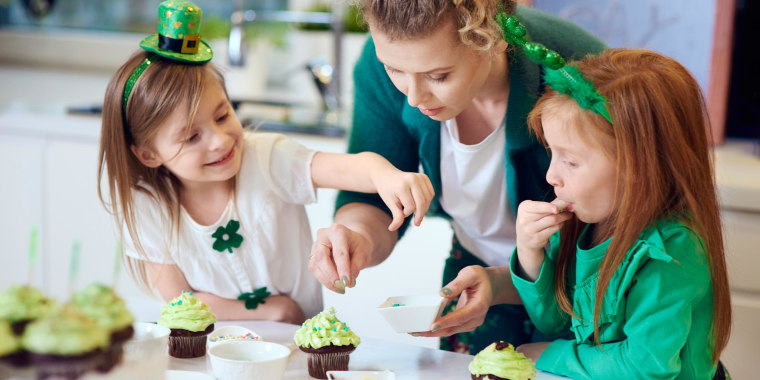 Mother and her daughters wearing St. Patricks Day decor and decorating cupcakes