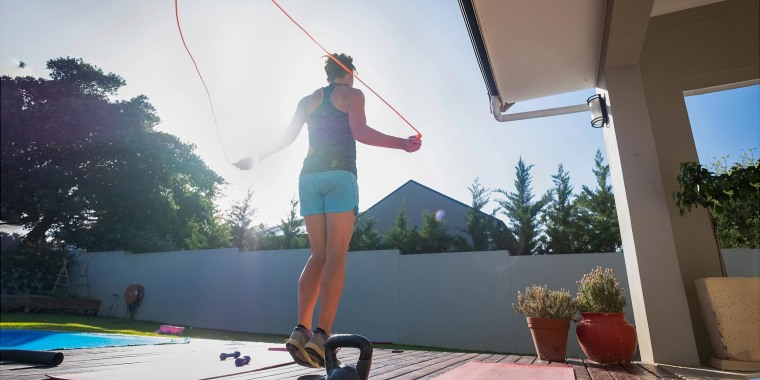 Woman jumping rope in her backyard while working out