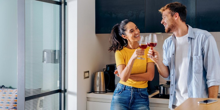 Woman and Man clinking glasses of red wine in a kitchen