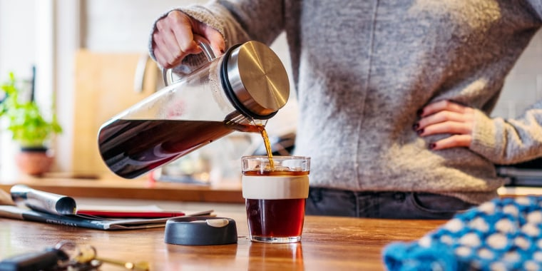 Woman pouring cold brew in her kitchen from her cold brew maker