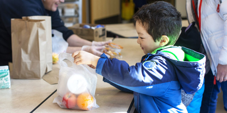 Tyden Brownlee, 5, picks up a free school lunch at Olympic Hills Elementary School on March 18, 2020 in Seattle, Washington.
