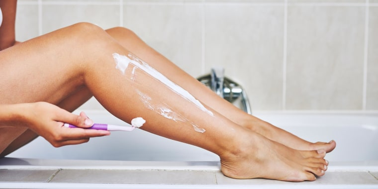 Woman shaving her legs in the bathroom