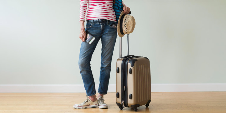 Woman in striped white and red shirt, holding a passport and suitcase