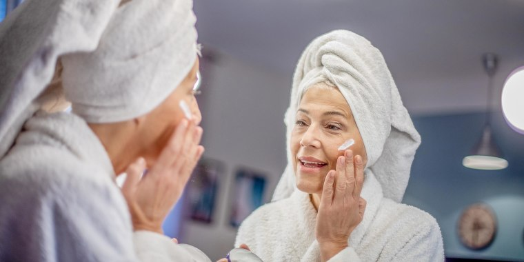 Woman rubbing anti aging eye cream while looking at herself in the bathroom