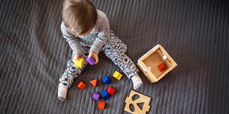 Little boy on a bead spread playing with shape blocks