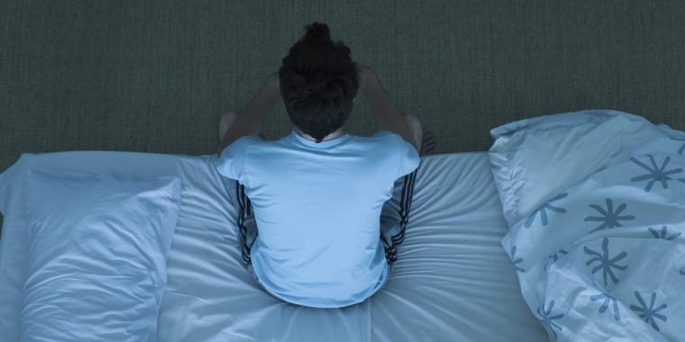 Man sitting on bed unable to sleep