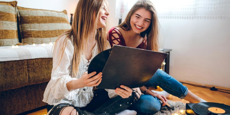 Two teenager girls enjoying a gift of records and portable record player