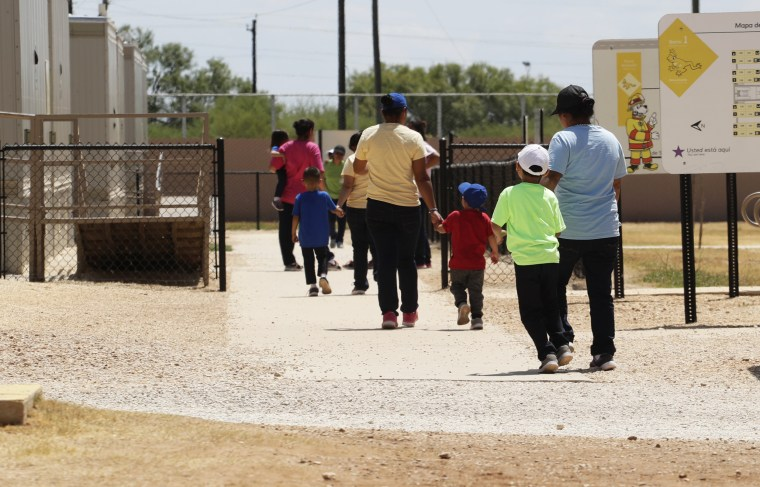 Immigrants seeking asylum hold hands as they leave a cafeteria at the ICE South Texas Family Residential Center in Dilley, Texas, on Aug. 23, 2019.