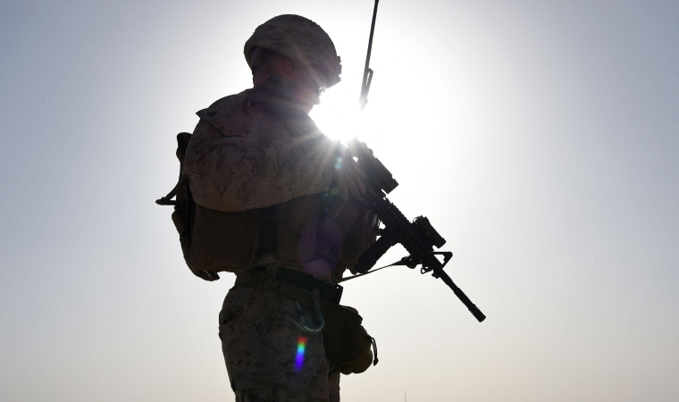 Image: A U.S. Marine watches Afghan Commandos take part in a combat training exercise at Shorab Military Camp in Lashkar Gah in Helmand province.