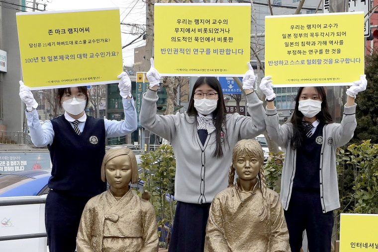 Image: High school students hold up banners to protest a recent academic paper by Harvard University professor J. Mark Ramseyer, behind statues symbolizing wartime sex slaves in Seoul, South Korea on Feb. 25, 2021.