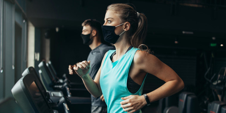 Woman and Man running on treadmills at the gym while wearing breathable face masks