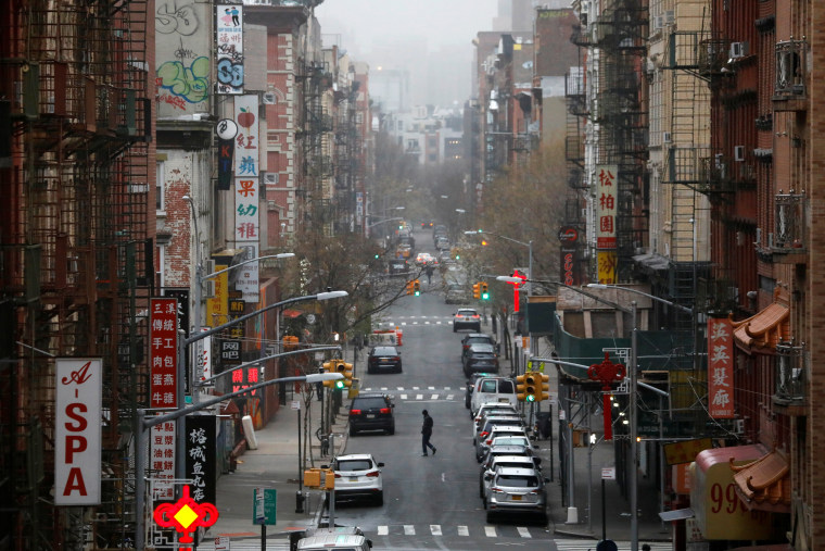 Image: A person crosses a street in Manhattan's Chinatown.