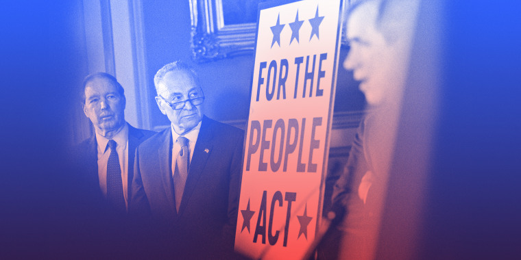 "Image: Chuck Schumer stands next to a board that reads,""For the People Act\""."