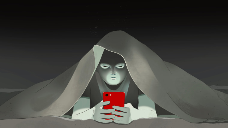 Image: A young boy looks at his phone under a blanket and shadows create a mask on his face.