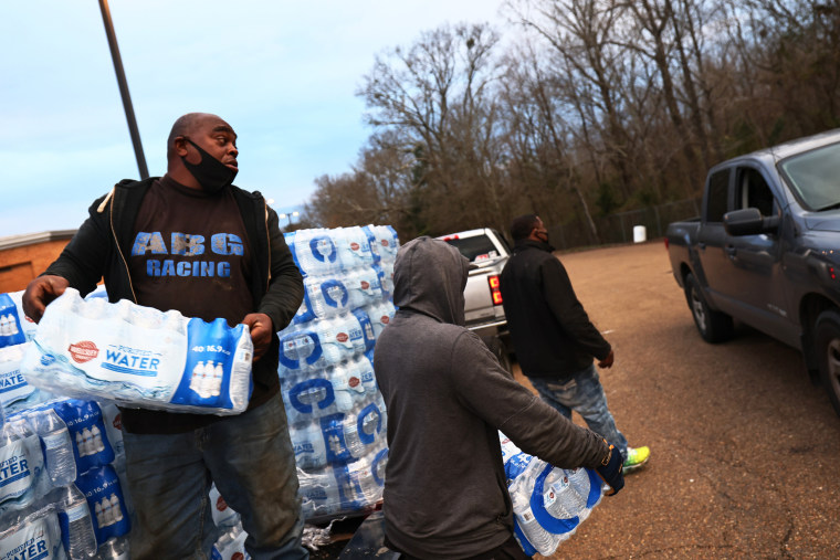 Benjamin Williams and Ben Mitchell help to distribute bottled water at a water distribution site in the parking lot of Forest Hill High School on March 5, 2021 in Jackson, Miss.