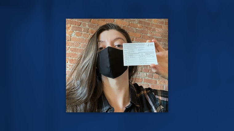 Image: Caira Conner holds her vaccination card