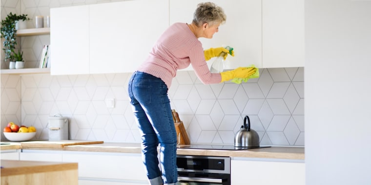 Woman standing on a stool in her kitchen cleaning the outside of her white kitchen cabinets