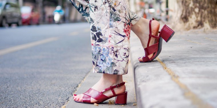 Image of a Woman wearing floral pants and stylish red sandals, walking off the curb