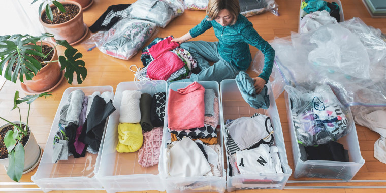 Woman sitting on her floor surrounded by clothes, organizing drawers and big storage bags for under her bed
