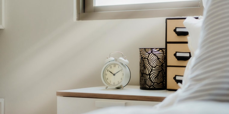 Lifestyle image of a bedroom with white old fashioned alarm clock on table next to bed
