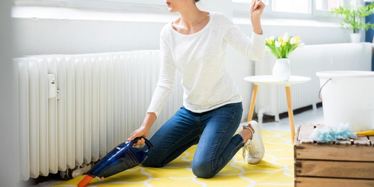 Woman vacuuming her yellow carpet while listening to music on her headphones