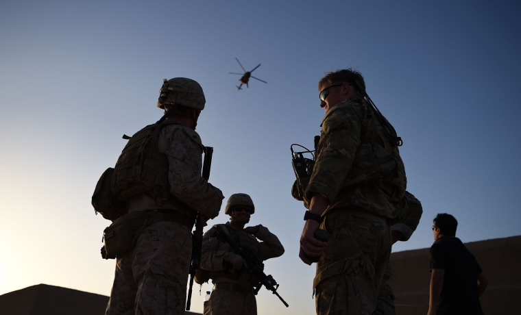 Image: U.S. Marines and Afghan Commandos stand together as an Afghan Air Force helicopter flies past during a combat training exercise at Shorab Military Camp in Lashkar Gah in Helmand province.