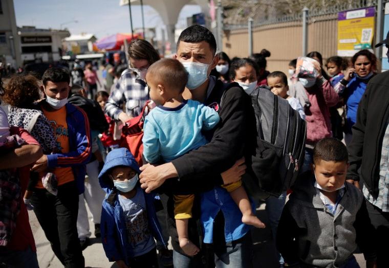 Migrants from Central America stand near the Paso del Norte international border bridge.