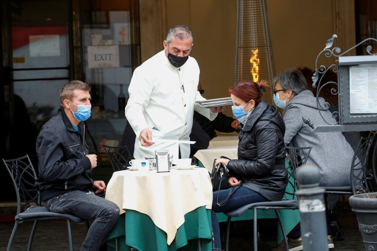Image: People enjoy their time at a bar on the final day of open restaurants and bars before tighter Covid-19 restrictions are enforced, in Rome, Italy