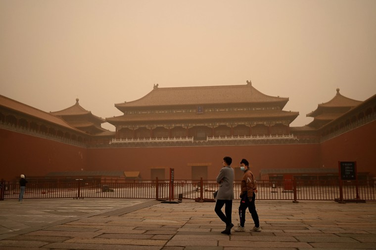 Image: People walk near the entrance of the Forbidden City during a sandstorm in Beijing