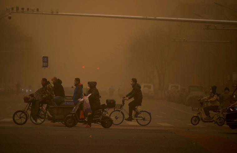 Image: People cross a street during a sandstorm in Beijing