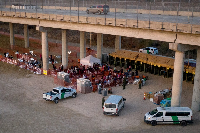 Image: Migrant families with children take refuge at a processing center under Anzalduas International Bridge in Granjeno, Texas