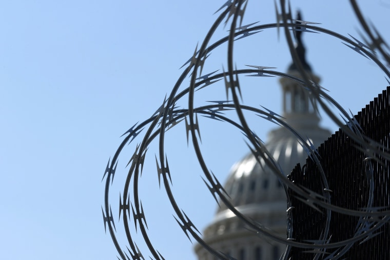 Image: A fence topped with razor wire surrounds the U.S. Capitol,