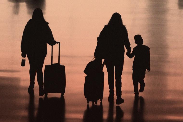 Travelers walk in Salt Lake City International Airport, Tuesday, March 9, 2021.