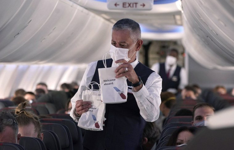 An American Airlines flight attendant hands out snack bags before a flight on Dec. 2, 2020.