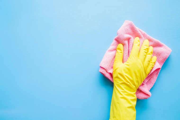 Employee hand in rubber protective glove with microfiber rag wiping blue table