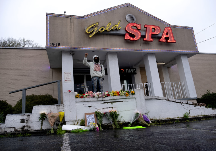 Image: Malik Peay stands in protest outside of Gold Spa in Atlanta, a day after three massage parlors were targeted by a shooter that left eight people dead, six of them Asian women.