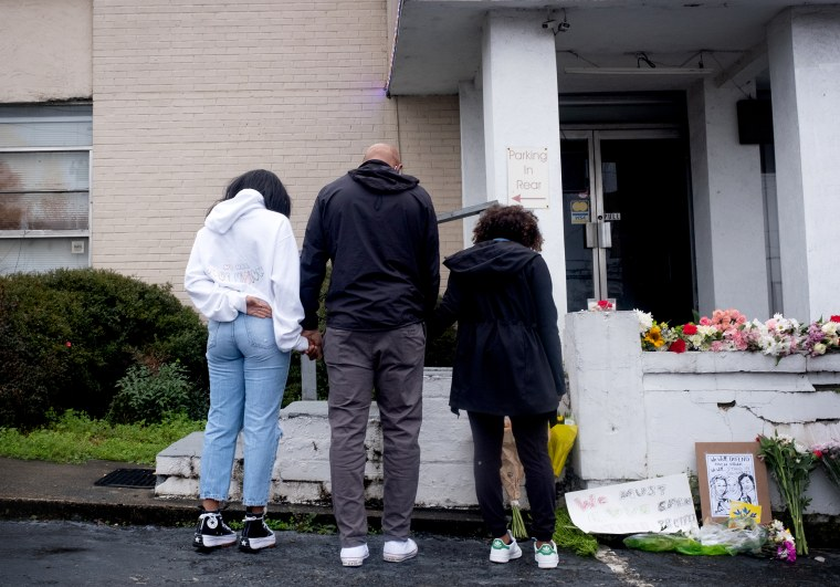 Image: Members of the Lavette family join hands and leave flowers at a memorial outside of Gold Spa in Atlanta on Wednesday.