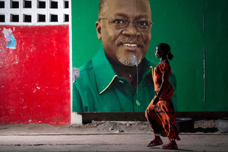 Image: A woman walks past an election billboard after ruling party Chama Cha Mapinduzi candidate John Magufuli in Dar es Salaam.