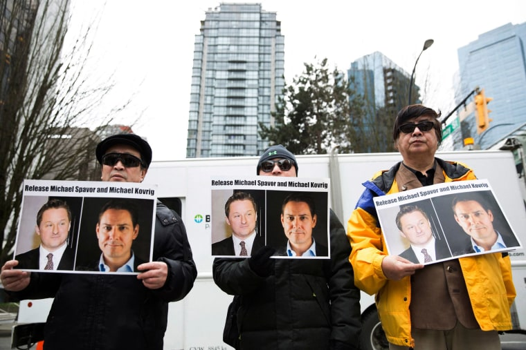 Image: Protesters hold photos of Canadians Michael Spavor and Michael Kovrig, who are being detained by China, outside British Columbia Supreme Court, in Vancouver.