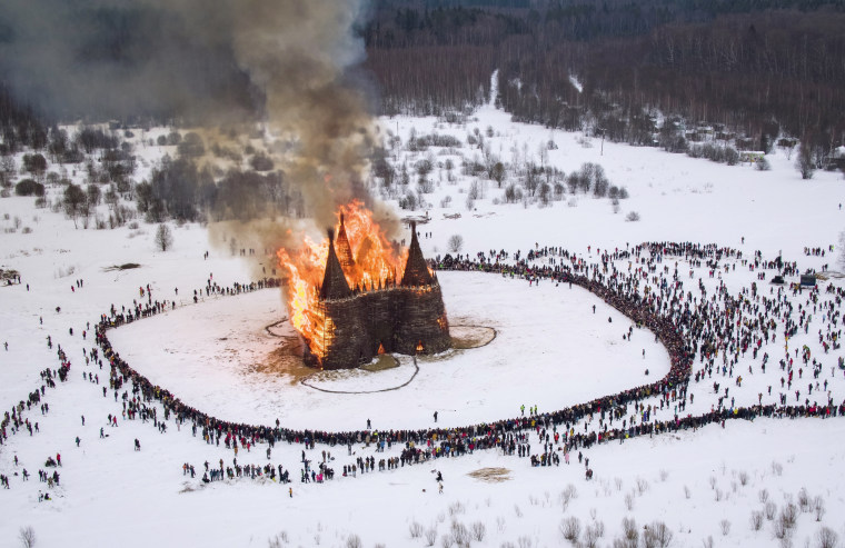 Image: Specators watch a wooden castle burning as part of the Maslenitsa (Shrovetide) festival in Nikola-Lenivets, on March 13, 2021. Maslenitsa is an Orthodox Christian holiday celebrated in the last week before the Orthodox Lent.